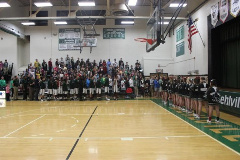 Before the game begins, the student section, basketball team, and cheerleaders honor America during the national anthem.