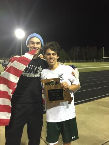 Senior midfielder, Chase Guerrero holds the 2015 District Championship plaque while celebrating with senior Green Pit member, Matt Marler.