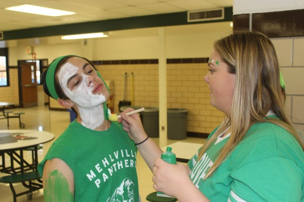 Senior, Chase Guerrero, gets his face painted by Amanda Fierst (12) before the varsity basketball game.