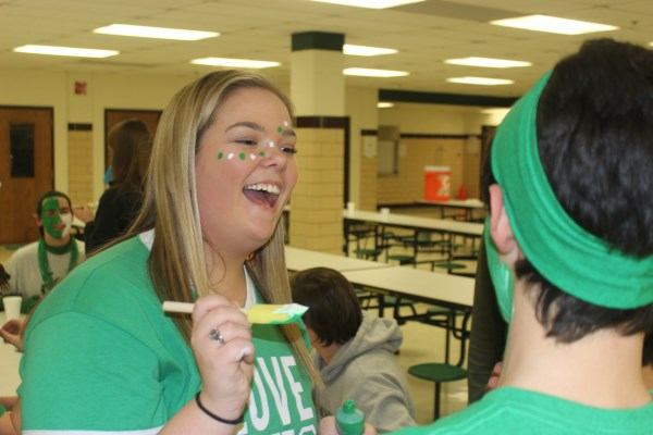 Senior, Amanda Fierst laughs while admiring the paint on senior. Chase Guerrero's, face.