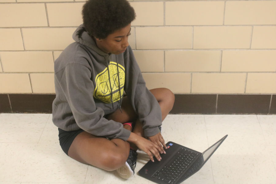 Asia Frazier working on  school work in the hallway.