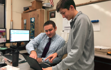 Wilhite helps a student with his laptop