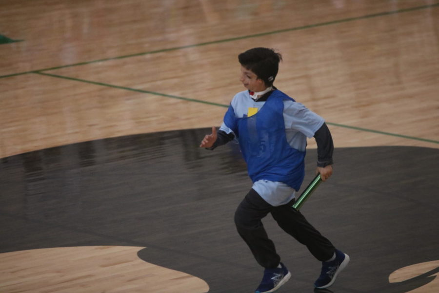 A middle school athlete runs as hard as he can in hopes of winning the relay race for his school.