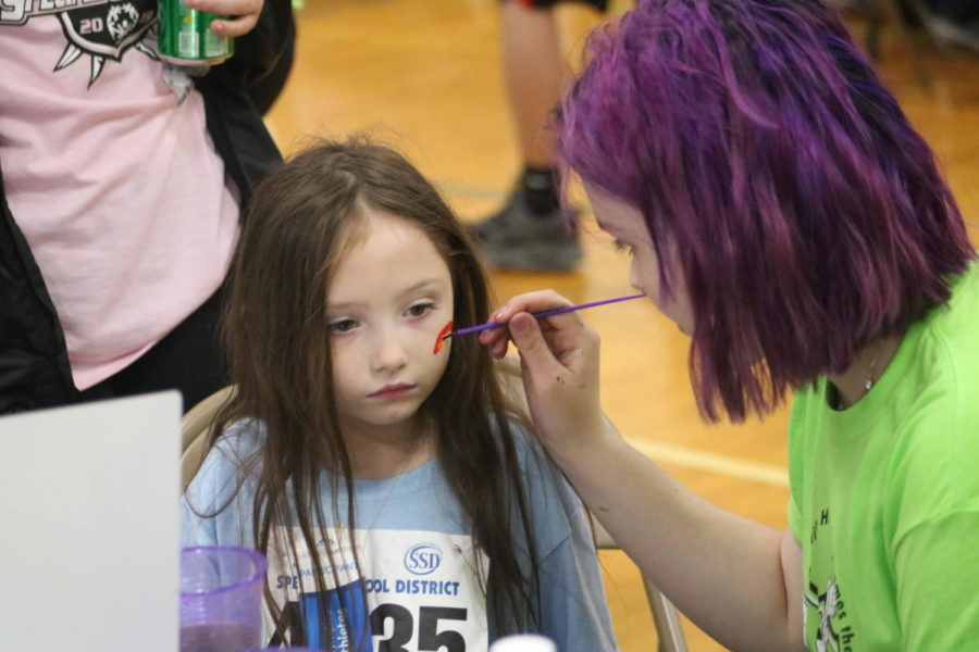 Mehlville Senior in the village paints on an athletes face as part of their booth.