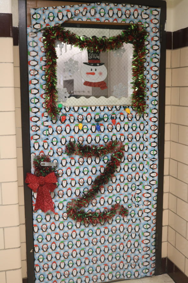 Ms. Zielinski decorates her door with penguin wrapping paper and garland.