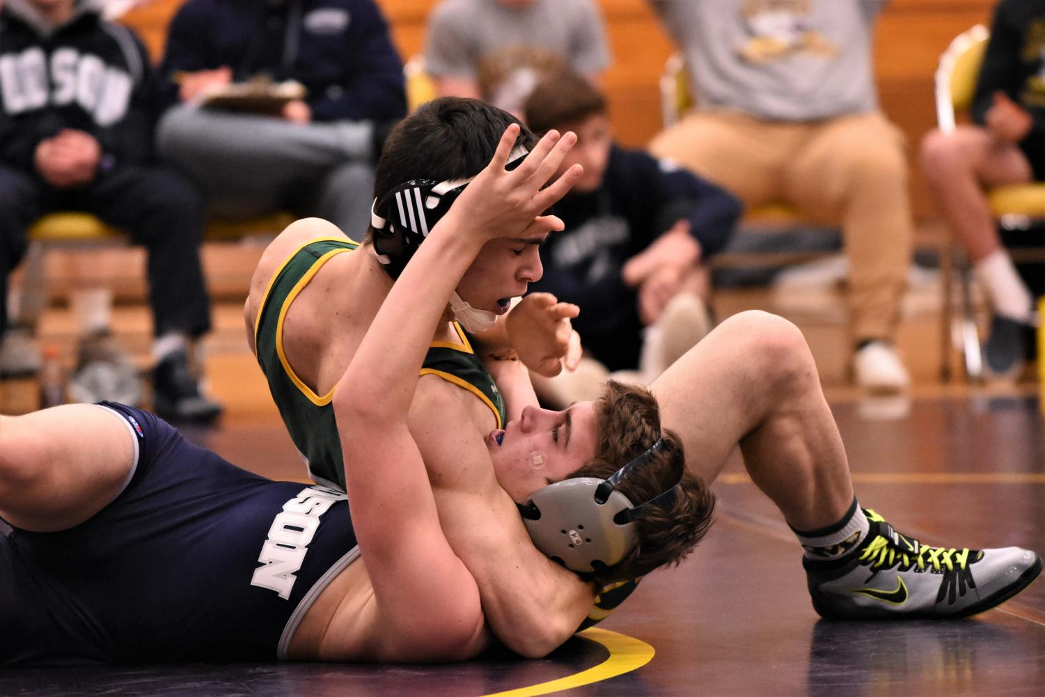 Wrestler pins opponent in head and arm pinning combination.